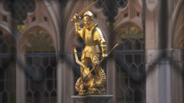 Pull focus onto a resplendent statue of St George slaying the dragon situated in the Dean's Cloister at Windsor Castle Berkshire UK FKAU104L Clip...