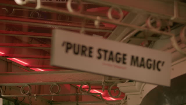 """pull focus onto a sign displaying a quote from a newspaper critic's review reading """"'pure stage magic' sunday telegraph"""", west end, london, uk. - critic stock videos & royalty-free footage"""