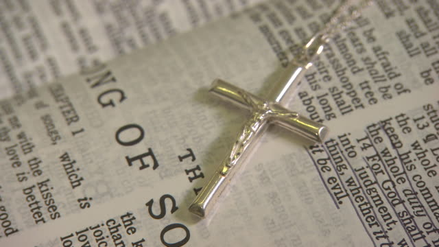 Pull focus onto a silver crucifix resting on an open page of the Bible.