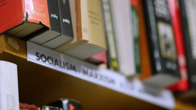 Pull focus onto a 'Socialism' sign on a bookshelf