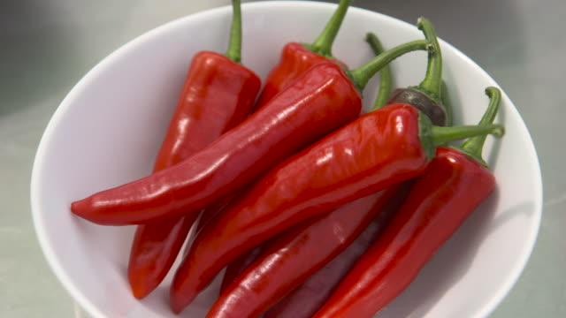 pull focus onto bowl of chillies, uk - chili schote stock-videos und b-roll-filmmaterial