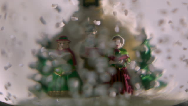 Pull focus onto carol singers and a church fashioned out of plastic in a snowglobe.