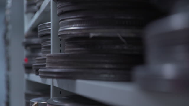 Pull focus onto stacks of film cans held on shelving units