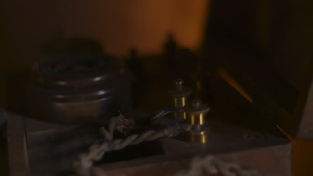 Pull focus over a WWI-era telegraph machine in warm candlelight inside a WWI trench dugout, northern France.