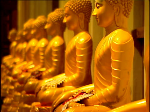 pull focus row of glistening gold buddhas to show further statues in distance temple of the tooth kandy - gold tooth stock videos & royalty-free footage