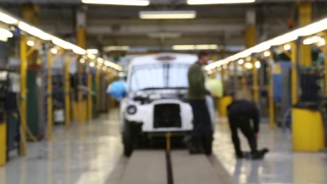 pull focus shot, a factory worker working on a car's undercarriage. workers inside the factory of the london taxi company attach the body of a tx4... - コベントリー点の映像素材/bロール