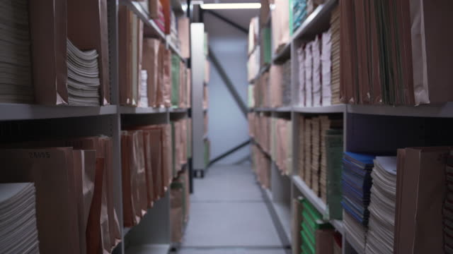 pull focus shot between two shelving units containing paper manuscripts - shelf stock videos & royalty-free footage