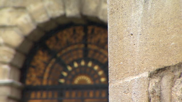 pull focus shot from brick work onto an archway at oxford university london - architecture stock videos & royalty-free footage