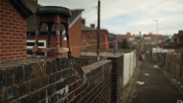 pull focus shot of a bar stool sitting on the top of a wall. derelict houses in stoke, up for auction on april 23, 2013 in stoke, england pull focus... - stool stock videos & royalty-free footage