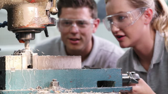 pull focus shot of engineer training female apprentice to use drill in factory - trainee stock videos & royalty-free footage