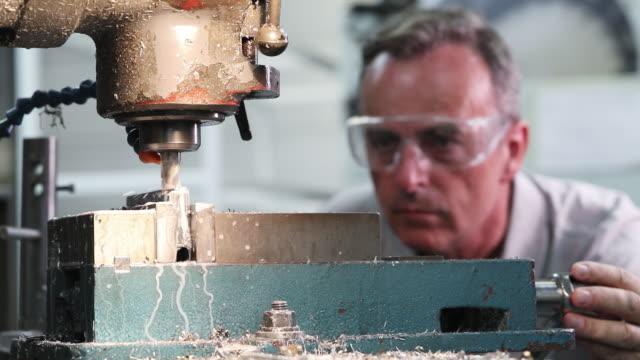 vídeos de stock, filmes e b-roll de puxe o foco tiro de engenheiro masculino usando broca na fábrica - só um homem maduro
