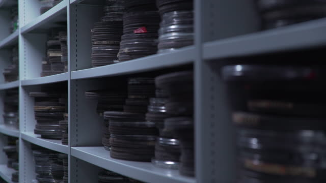 Pull focus shot of metal film cans on a shelving unit