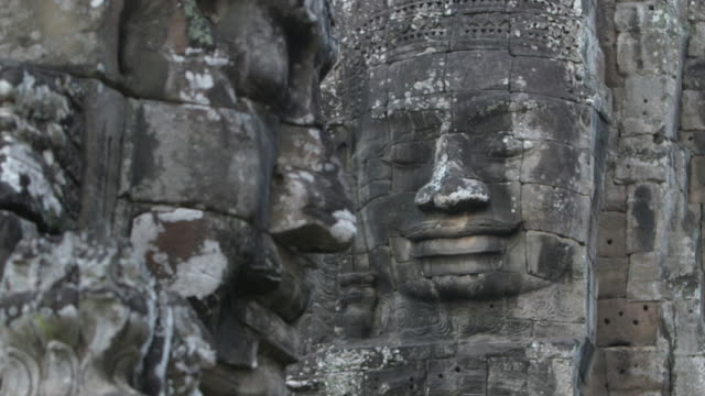 Pull focus shot on a large stone faces, decorating the exterior of the Bayon temple at Angkor.
