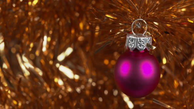 pull focus shot on a pink bauble decorating a gold christmas tree. - tinsel stock videos & royalty-free footage