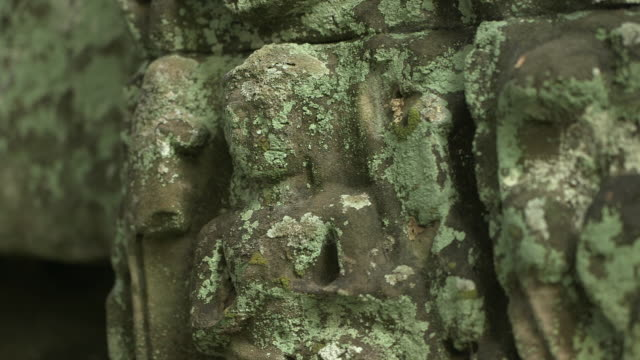 pull focus shot on a worn stone carving of a person on the exterior of the bayon temple at angkor. - 地衣類点の映像素材/bロール