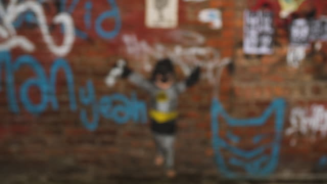 vídeos de stock e filmes b-roll de pull focus shot onto street art depicting a child in a 'batman' outfit in the northern quarter, manchester - rack focus