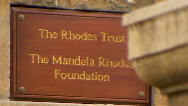 pull focus shot onto the 'the rhodes trust' sign on the brick work of rhodes college, oxford - 20 24 years stock videos & royalty-free footage
