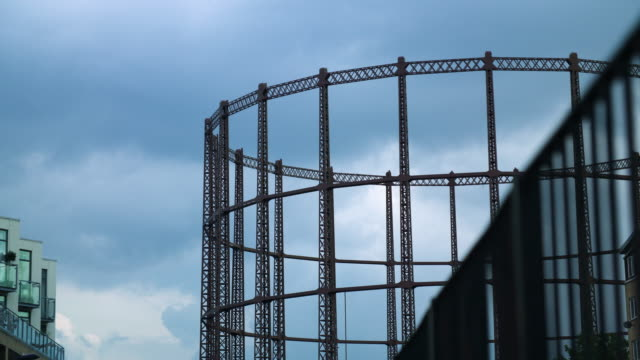 pull focus silhouette of gas holder against cloudy sky - rack focus stock videos & royalty-free footage