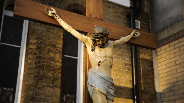 pull focus statue of jesus on the cross outside church, london - fade in video transition stock videos & royalty-free footage