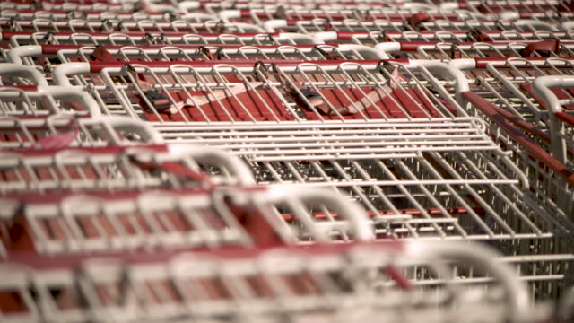 pull focus then pan left over shopping trolleys stacked outside a costco warehouse usa fkax253n clip taken from programme rushes ablb597x - in a row stock videos & royalty-free footage