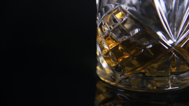 pull focus to cut glass tumbler filling up with scotch whiskey - cut video transition stock videos & royalty-free footage