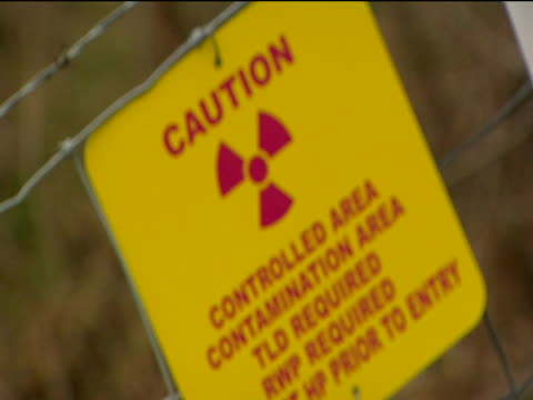 pull focus to red and yellow warning sign on barbed wire fence warning of a contamination area. - hygiene stock videos & royalty-free footage