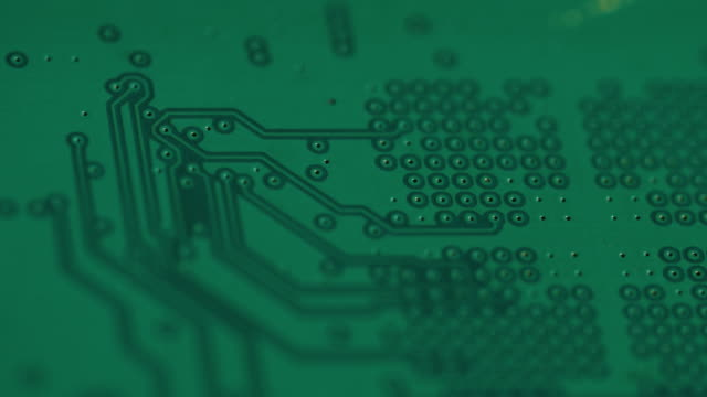 pull focus towards camera across a flat green circuit board. - electricity stock videos & royalty-free footage