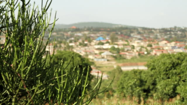 Pull focus tracking shot over the city of Kigali.