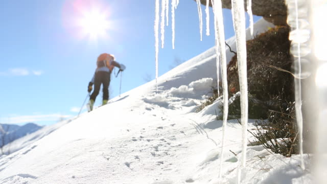 Pull focus view as ski mountaineer ascends snow slope, past icicles