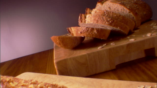 Pull out from a sliced loaf of bread to another loaf on a wooden cutting board.