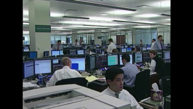 AVAILABLE ** Pull out from Lehman Brothers sign on wall of trading room to traders working at desks computers and on phones in New York US on...