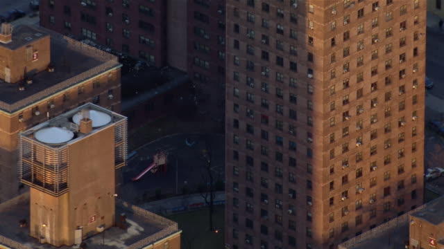 Pull out from playground in public housing project to aerial view of high rise apartment buildings in the Bronx, New York City.