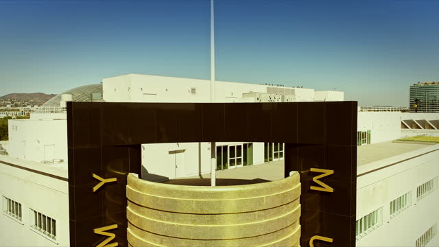 pull out from roof of black marble framed gold-tiled cylinder corner of the academy museum of motion pictures formerly a department store structure built in 1939 in streamline moderne style - academy of motion picture arts and sciences stock videos & royalty-free footage