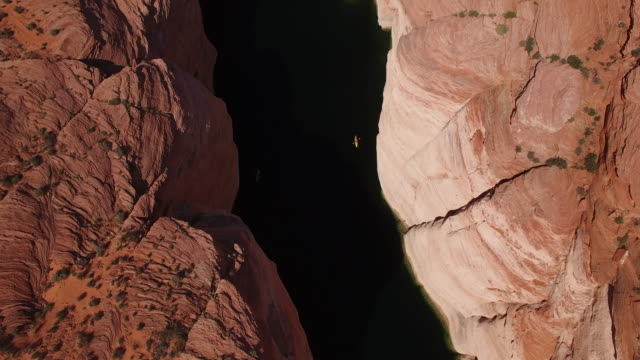 vídeos de stock e filmes b-roll de pull up looking down kayakers on lake powell 4k, drone aerial view of kayak and boat on lake powell reservoir and colorado river, with beautiful sand stone formations and water grand canyon located in glen canyon, arizona - grand canyon
