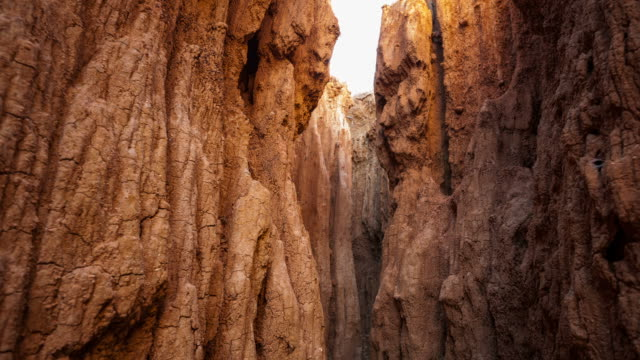 Pull-back linear timelapse from inside a cave of abstract eroded rock formations and sand full of texture and grain with changing light at sunrise