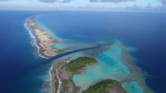 stockvideo's en b-roll-footage met pulling back over atoll lagoon entrance in sunset - frans polynesië