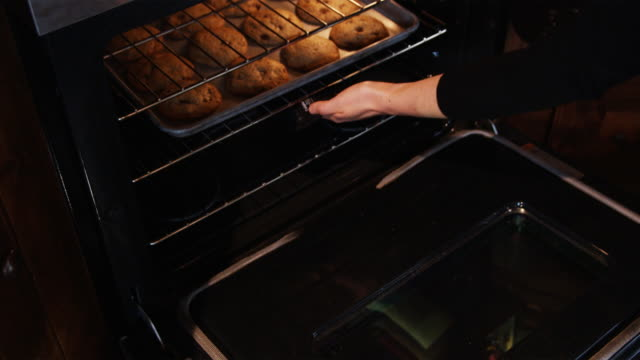 pulling cookies out of the oven - cookie stock videos and b-roll footage