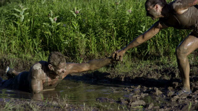 pulling friend out of mud - survival stock videos & royalty-free footage