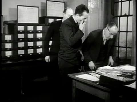 pulling out file from cabinet. inspector finch' at desk w/ men looking at file. opening file mug shots 'criminal record william mead.' finch' at desk... - 1949 bildbanksvideor och videomaterial från bakom kulisserna
