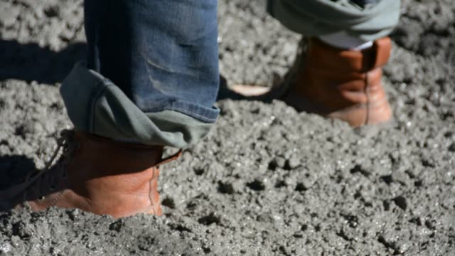 Pullout from heavy leather work boots standing in fresh concrete to cement workers