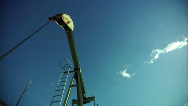 vídeos de stock, filmes e b-roll de ms, la, pump jack turning slowly against clear sky, california, usa - movimento perpétuo