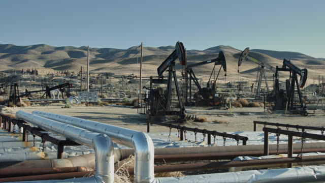 pump jacks by rolling desert hills - pipe stock videos & royalty-free footage
