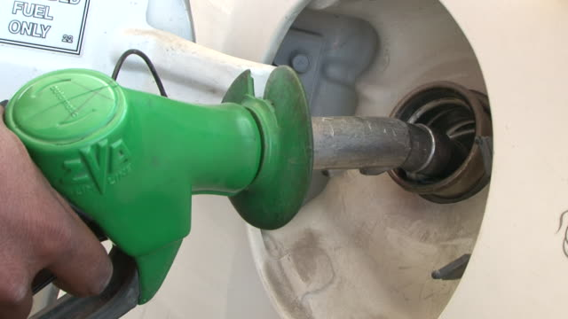 pumping gas. view of a man's hand placing a gas nozzle into the fuel tank of a car. - refuelling stock videos & royalty-free footage