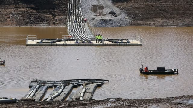 pumping out water from toddbrook reservoir above whaley bridge in derbyshire. torrential rain lead the dam to overflow causing extensive damage to the structure. fearing the dam could collapse, 1500 residents below were evacuated for around a week while t - out take stock videos & royalty-free footage