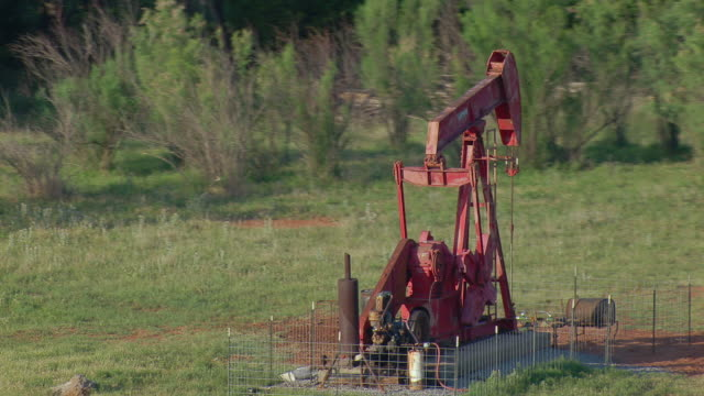 vidéos et rushes de pumpjack at oklahoma oil well - tour de forage