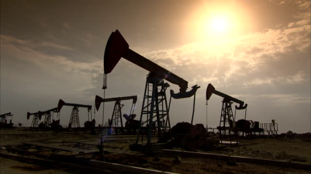Pumpjacks move up and down in an oil field at golden hour. Available in HD.