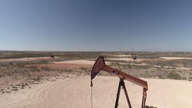 vídeos de stock e filmes b-roll de pumpjacks operating on oil wells in the permian basin oil field near crane tx usa on friday march 2 2018 - movimento perpétuo