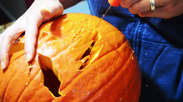 stockvideo's en b-roll-footage met pumpkin carving for halloween - snijwerk