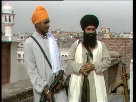 stockvideo's en b-roll-footage met punjab sikhs; ** upitn ng 7.3.84 ** india: punjab: amritsar: ext armed sikhs outside golden temple var shots weapons carried by sikhs sikh army... - var