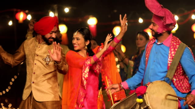 punjabi couple dancing in lohri festival, punjab, india - インド人点の映像素材/bロール